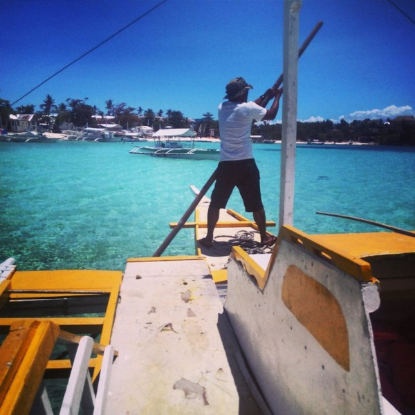 Dennis maneuvering the boat using a bamboo pole