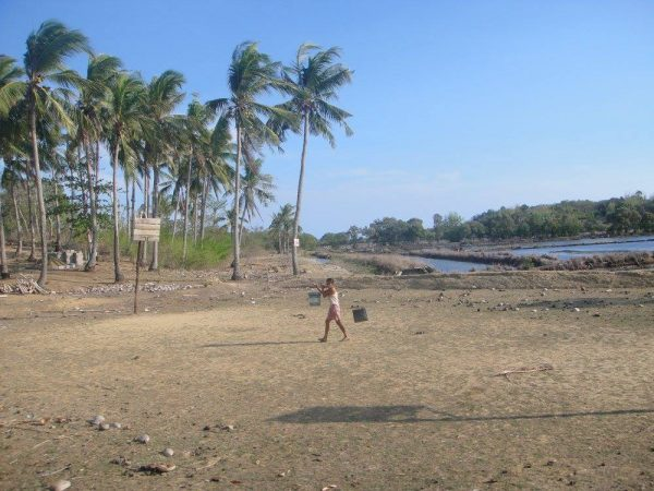 A woman in Sibunag carries buckets of water for her family