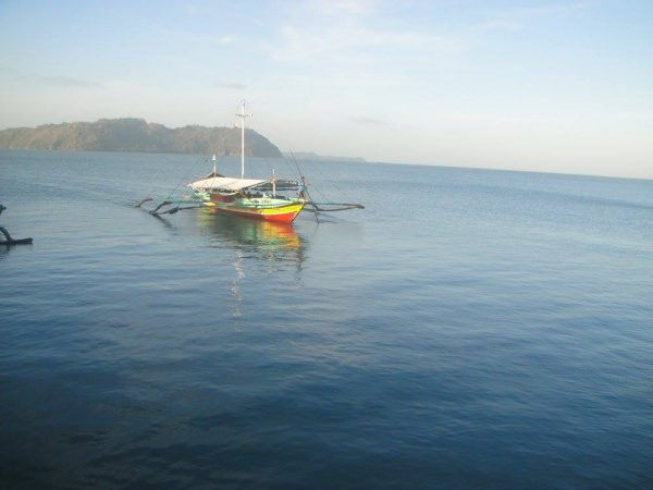 The verdant Guimaras Island offers a beautiful backdrop to the colorful boats crossing the Iloilo Strait
