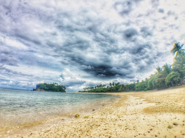 The powdery sand, blue sea and green beachfront amidst a cloudy sky
