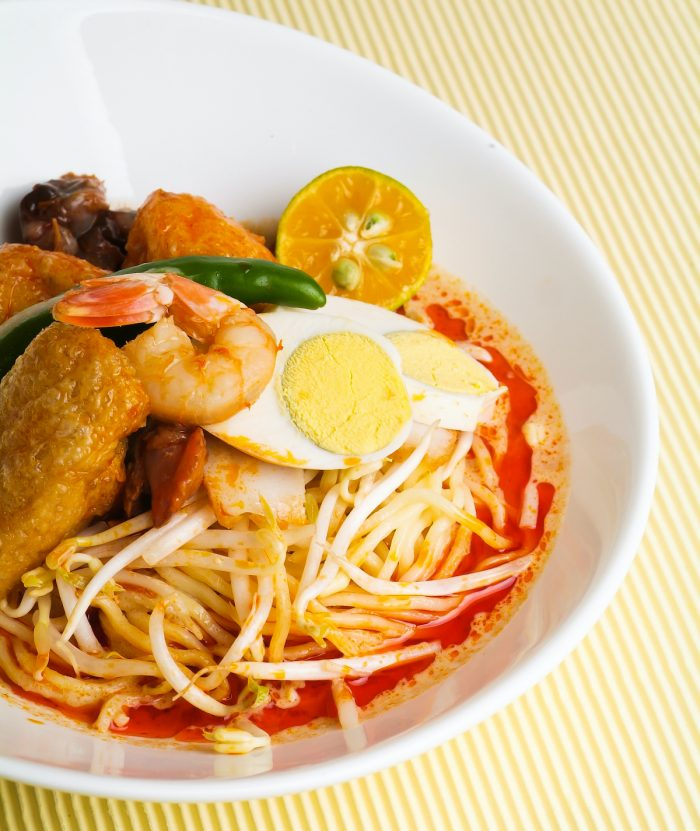 Curry Laksa which is a popular traditional spicy noodle soup photo via Depositphotos