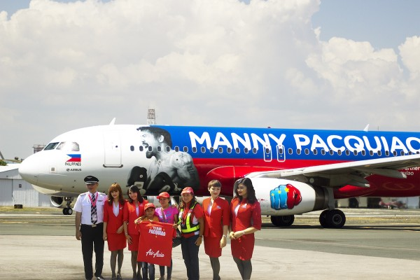 AirAsia Philippines Chairperson Maan Hontiveros (6th from left) gives a souvenir shirt to Pacman fans, Cathy Cabardo and her son, James, who flew from Cebu City to Manila on a sponsored flight aboard AirAsia Philippines Airbus A320 with the exclusive Manny Pacquiao livery.