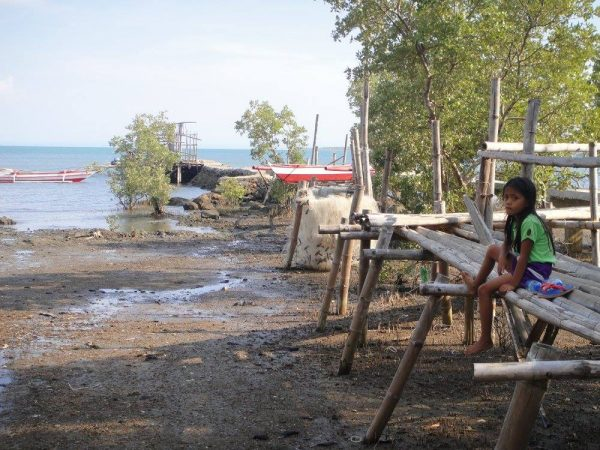 A girl sits on the bridge at the mangrove planting site - Mangroves in Guimaras