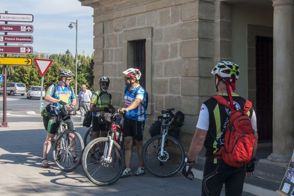 Cyclists from South America check their gear at the info station before crossing the bridge in Logrono.