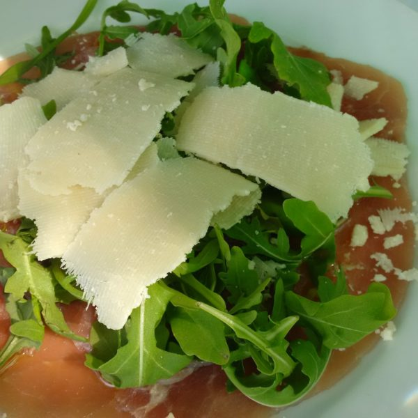 Carpaccio di Manzo with Rucola and Shaved Parmesan, a typical food by the lake
