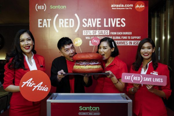 AirAsia Group Head of Brand Rudy Khaw and (RED) Chef Ambassador Hong Thaimee launching the new INSPI(RED) Burger flanked by cabin crew