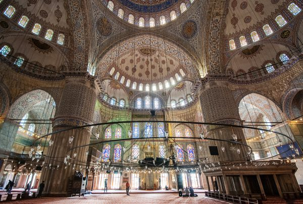 A circular lighting chandelier floats above the main hall of the mosque.