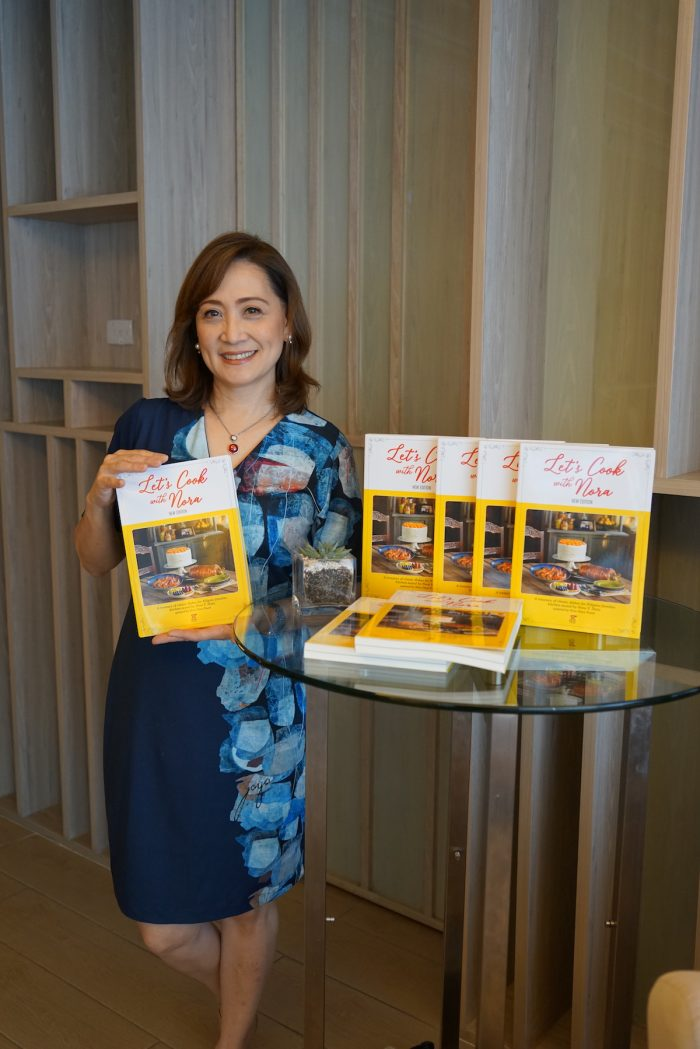 Nina Daza-Puyat showing the latest version of the cookbook Let's Cook with Nora