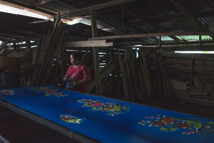 Local Kelantanese woman coloring the batik outlined by wax. The shot was taken at one of the villages in Kelantan that practices the traditional ways of producing batik.