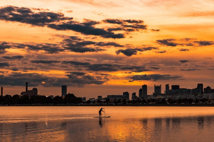 landscape photography of silhouette of man on boat near city buildings by @alexiby via Unsplash