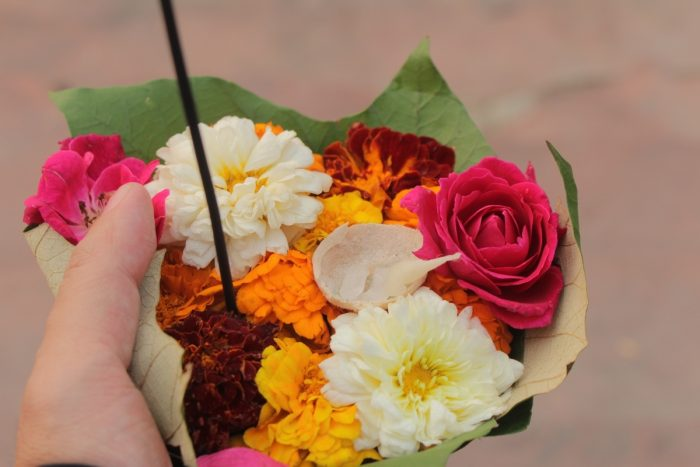 The writer holds a small diya filled with flowers to offer to the Ganges River
