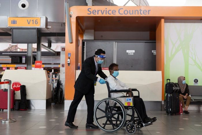 A Guest Service Agent assisting to transport a guest on a wheelchair.