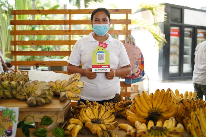 A merchant showcases her store's PayMaya QR which enables her to accept cashless payments from customers - promoting safer transactions at the Harvest to Goodness weekend market until July 30, 2020.