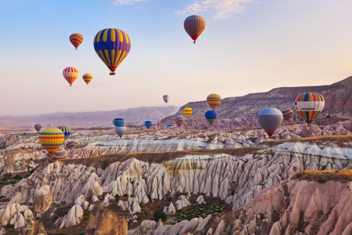 Hot air balloon flying over Cappadocia Turkey photo via Depositphotos