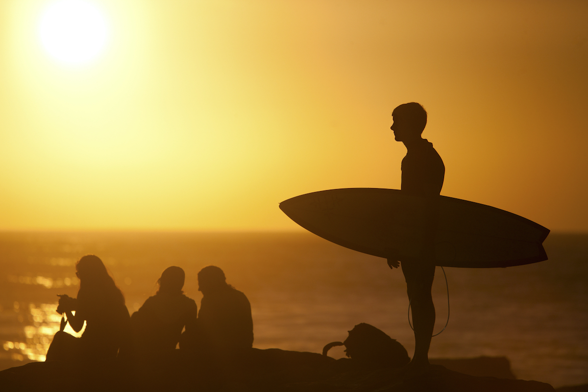 Surfer carrying surfboard on beach at sunset, Taghazout via Depositphotos