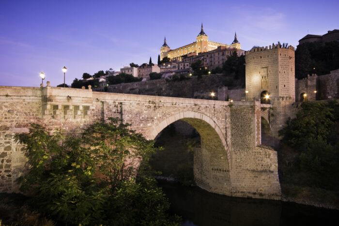 Panorama of the alcazar above the medieval San Martin bridge - Toledo, Spain photo via Deposit Photos