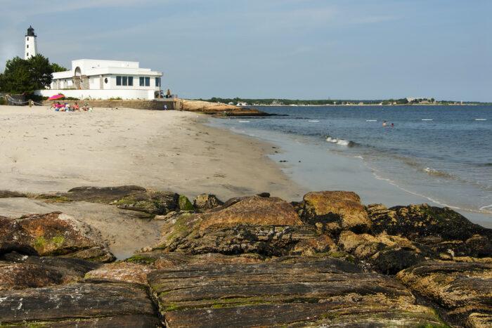 Beach Surrounds Lighthouse in Connecticut photo via Depositphotos