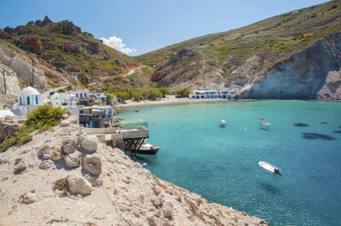 Crystal clear water of Firopotamos beach at Milos island photo via Depositphotos