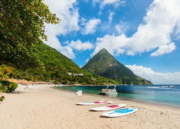 Idyllic white sand tropical beach with view to Piton mountains in Saint Lucia photo via Depositphotos