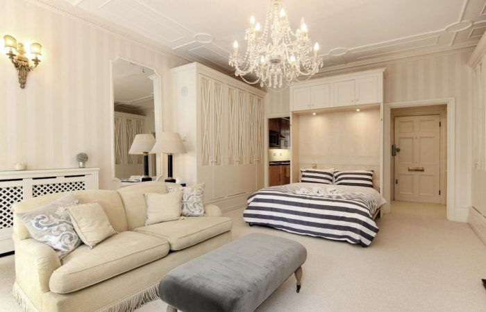 The living area and sleeping area in the large, elegant studio apartment rental in London