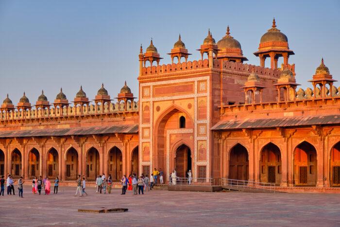Tourists visiting Jama Masjid mosque in Fatehpur Sikri, Agra, India photo via Depositphotos