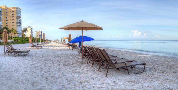Umbrellas and chairs on Vanderbilt Beach photo via Depositphotos