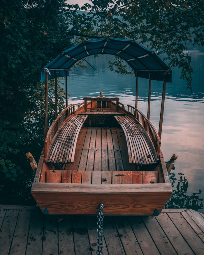 Wooden Boat docked at Lake Bled Boardwalk photo by Szymon Fischer via Unsplash