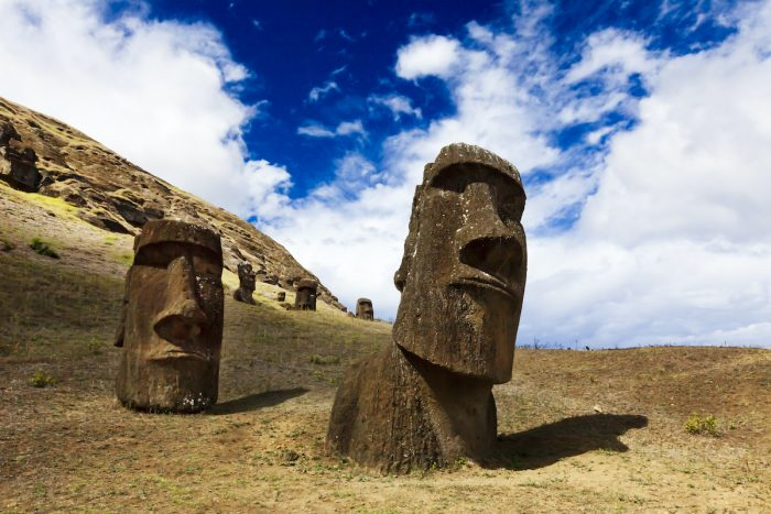Heads of buried moais standing on a mountain in Easter Island photo via DepositPhotos