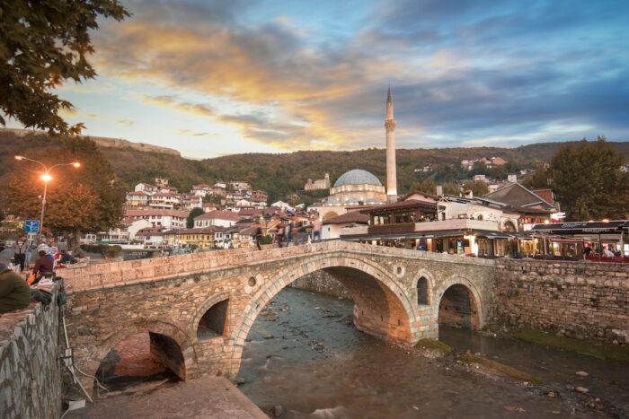 Sunset view of old stone bridge and old Ottoman Sinan Pasha Mosque photo via Depositphotos