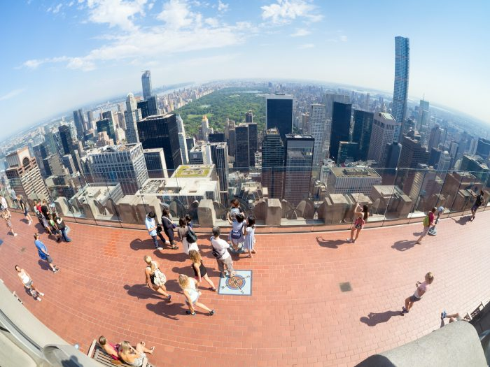 Tourists at the Top of the Rock observation Deck atop the GE Building in New York photo via Depositphotos