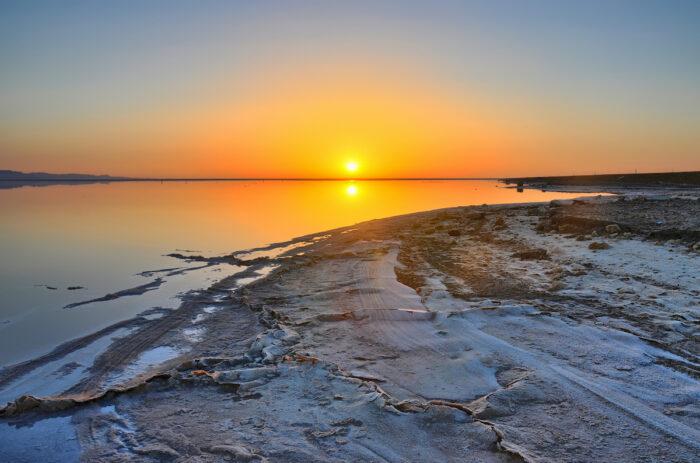 Beautiful sunrise on salt lake Chott el Djerid, Sahara desert, Tunisia photo via Depositphotos