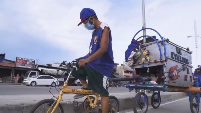 With his bike, Joey Belo spends long days pedalling around the city and distributing bags of toys and snacks to street children.  (Screenshot from Bike Camper JBelo's YouTube video)