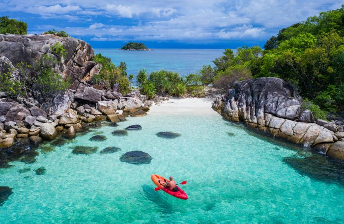 Aerial drone view of in kayak in crystal clear lagoon sea water during summer day near Koh Lipe island in Thailand photo via Depositphotos