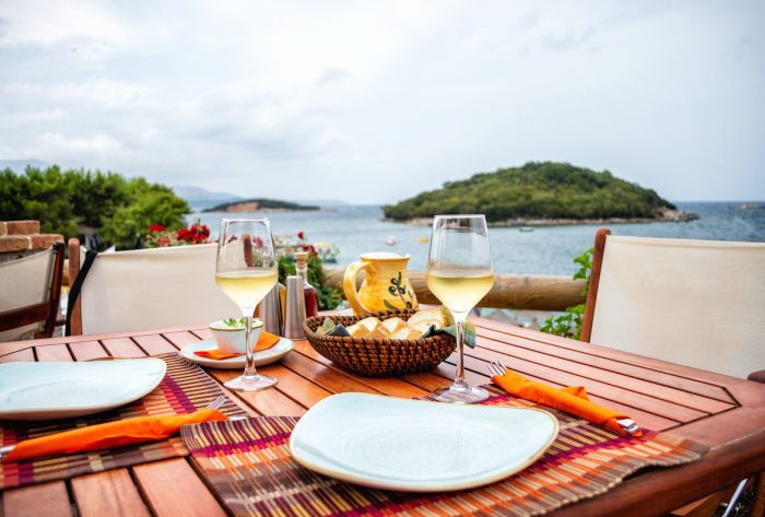 Restaurant with served table in seafront of Ionian sea, Ksamil photo via Depositphotos
