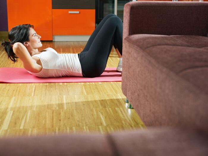 Woman doing abs exercise at home photo via Depositphotos
