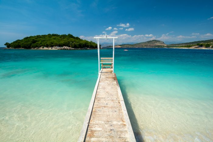 Wooden pier on paradise beach in Ksamil in Albania photo via Depositphotos