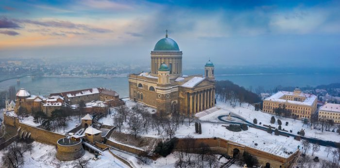Aerial panoramic view of the beautiful snowy Basilica of Esztergom with Slovakia at the background on a foggy winter morning photo via Depositphotos