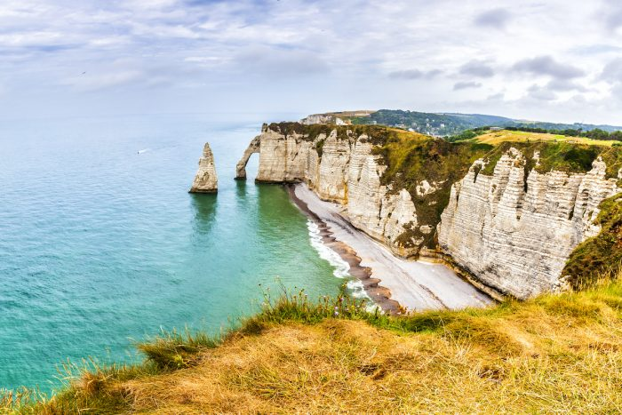 Panorama of natural chalk cliffs of Etretat with visible arche and beach coastline photo via Depositphotos.