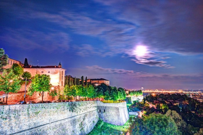 Stone walls of Castle La Rocca in Bergamo old town, Italy under the night lights