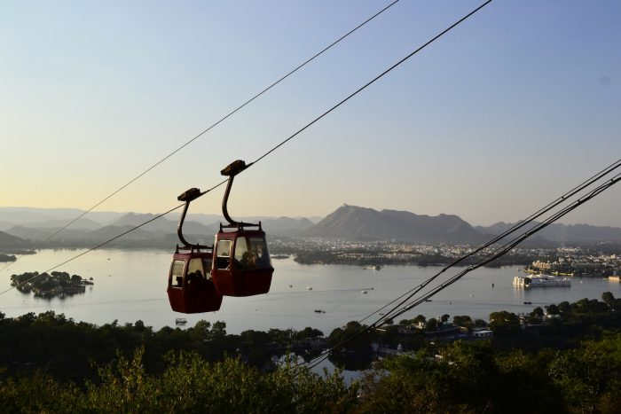 Two hanging cabins of Mansapurna Karni Mata Ropeway and panoramic view to the Pichola Lake with clear blue sky, Udaipur, Rajasthan, India photo via Depositphotos