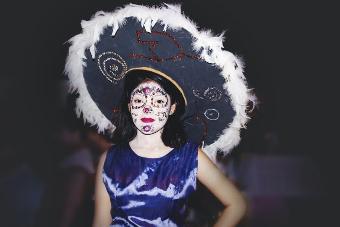 Woman dressed as catrina with flower skull make up and big hat with feather for day of the dead photo via Depositphotos