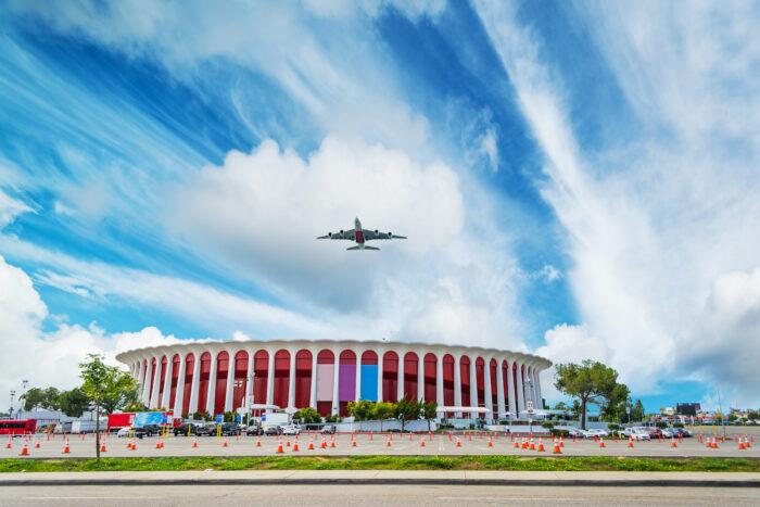 Airplane flying over Great Western Forum photo via Depositphotos