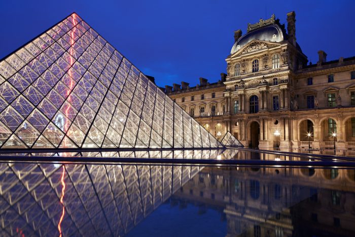 Louvre museum and pyramid night view in Paris photo via Depositphotos