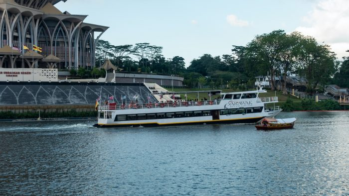 Sarawak River Cruise boat cruising along Sarawak River in Kuching Waterfront photo via Depositphotos