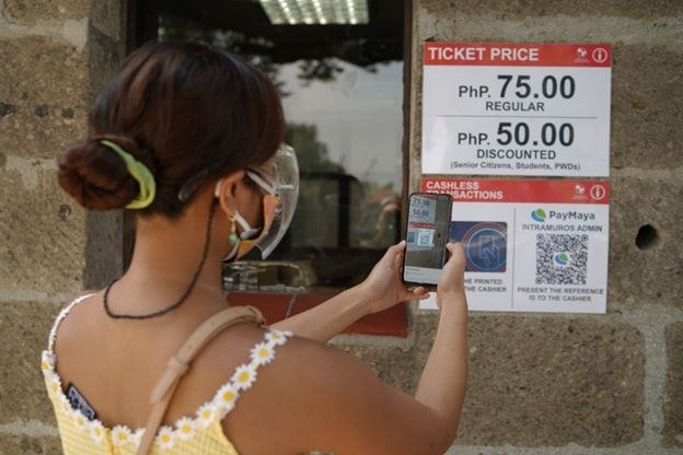 The Department of Tourism and the Intramuros Administration have announced the re-opening of select sites and museums in the walled city of Intramuros to the public as part of their efforts to re-ignite domestic tourism and boost the recovery of the local economy. In this photo, a visitor is scanning the PayMaya QR code displayed at ticketing booths using their phone to pay contactless for tickets and other admission costs as part of the minimum health standards being observed in Intramuros.