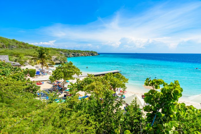 Porto Marie beach with white sand and crystal clear blue water in Curacao photo via Depositphotos
