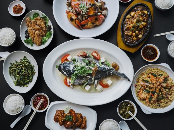 An appetizing and mouth-watering array of Zi Char dishes are laid out for sharing, with seafood, meat, and vegetable dishes including rice and soup. The variety of dishes on display point to the diversity of influences and flavors that make-up the Zi Char cooking style.