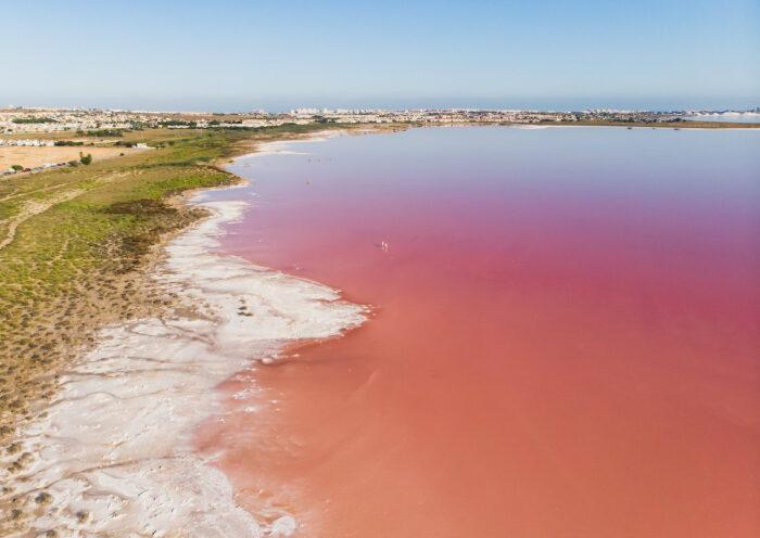 Beautiful aerial wide vibrant summer view of las Salinas de Torrevieja, The Pink Lake Of Torrevieja photo via Depositphotos